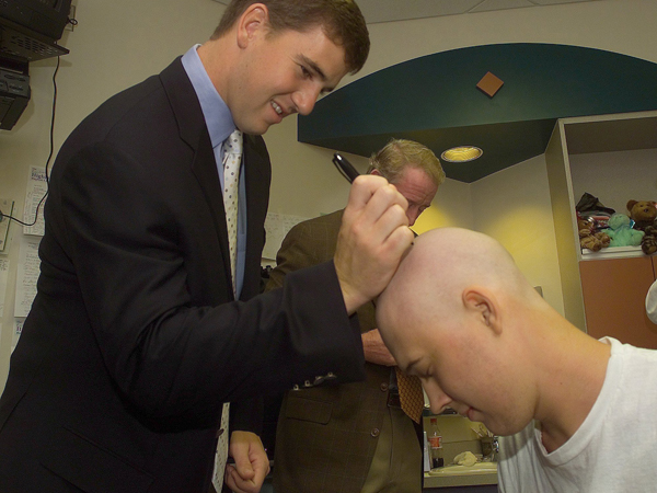 Eli signs the head of Batson patient Justin Scruggs during a visit to the children's hospital in 2004, his rookie year. Eli would write about the impromptu autograph in a letter published in The Players' Tribune. (Courtesy The Clarion-Ledger)