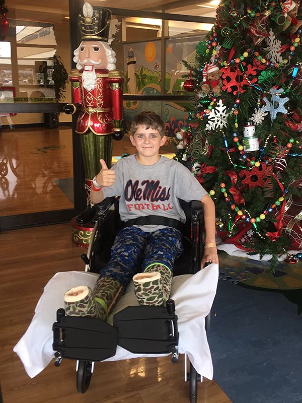 "Felton gives a ""thumbs-up"" sign in front of the Batson Children's Hospital's Christmas tree while recovering from major orthopaedic surgery last December."