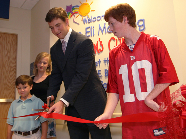In 2009, Eli cuts the ribbon for the Eli Manning Children's Clinics with help from Batson Children's Hospital patients, from left, Cameron Smyly, Aubree Jordan, and Taylor Gibson.
