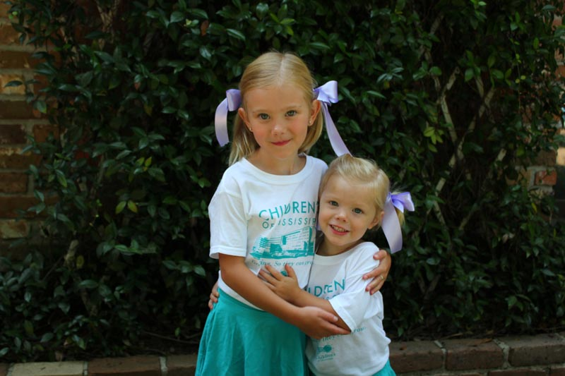Young, smiling sisters embrace in their new Children's of Mississippi t-shirts.