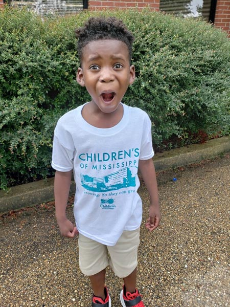 Elementary school-age boy hams it up as he sports a new Children's of Mississippi t-shirt.