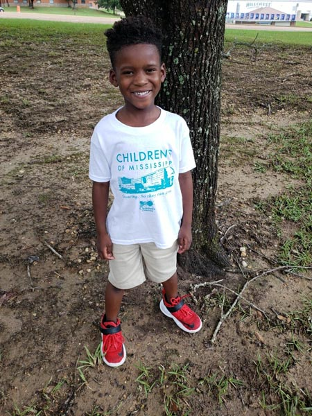 Elementary school-age boy flashes a big smile as he sports a new Children's of Mississippi t-shirt.