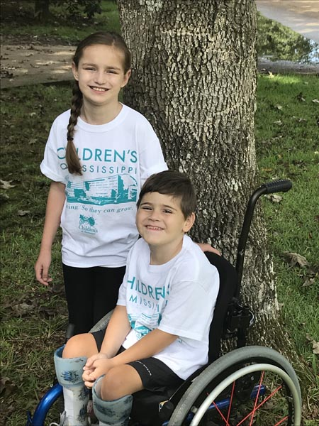 Wearing new Children's of Mississippi t-shirts, a proud older sister stands beside her little brother in his wheelchair.