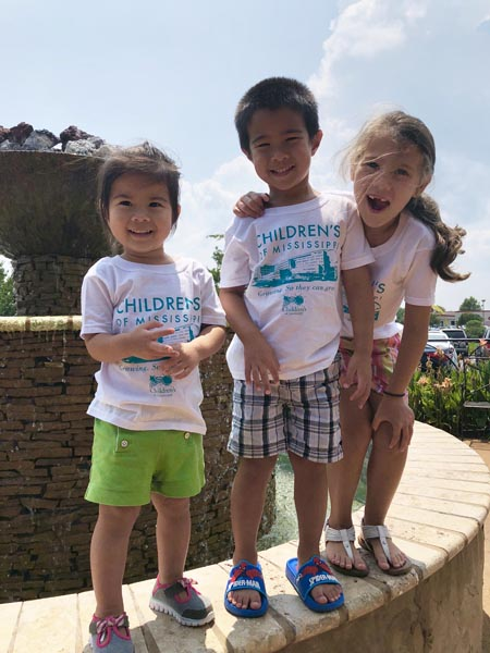 Three children proudly display their new Children's of Mississippi t-shirts as they pose at the edge of a rock fountain.